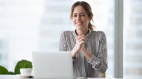Hopeful woman in front of laptop