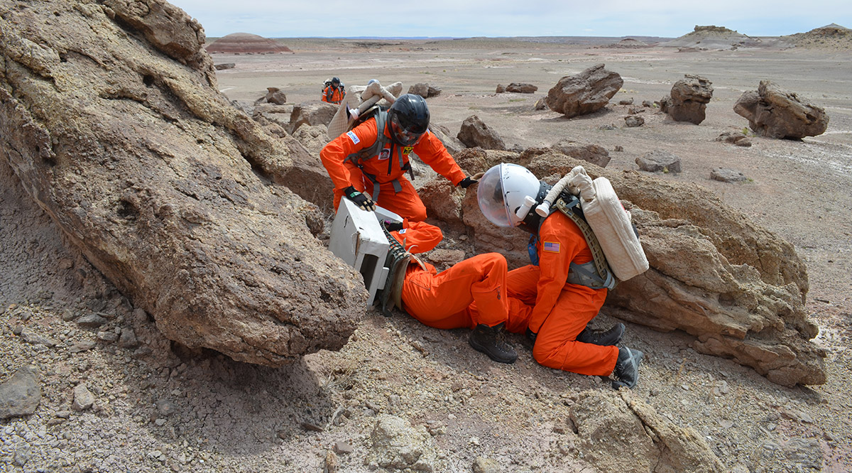 people in spacesuits on beach