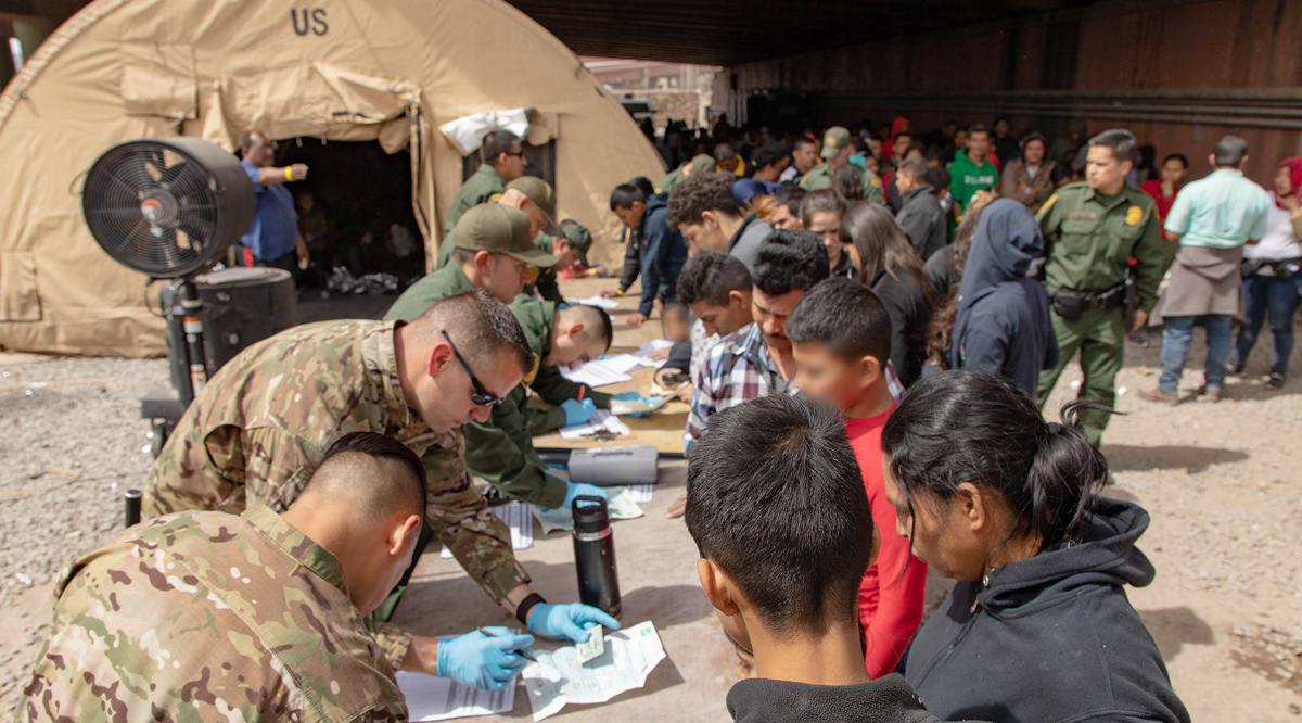 American soldiers filling up forms for migrants at a processing center.