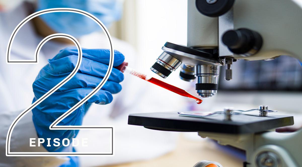 A researcher putting a drop of liquid underneath a microscope