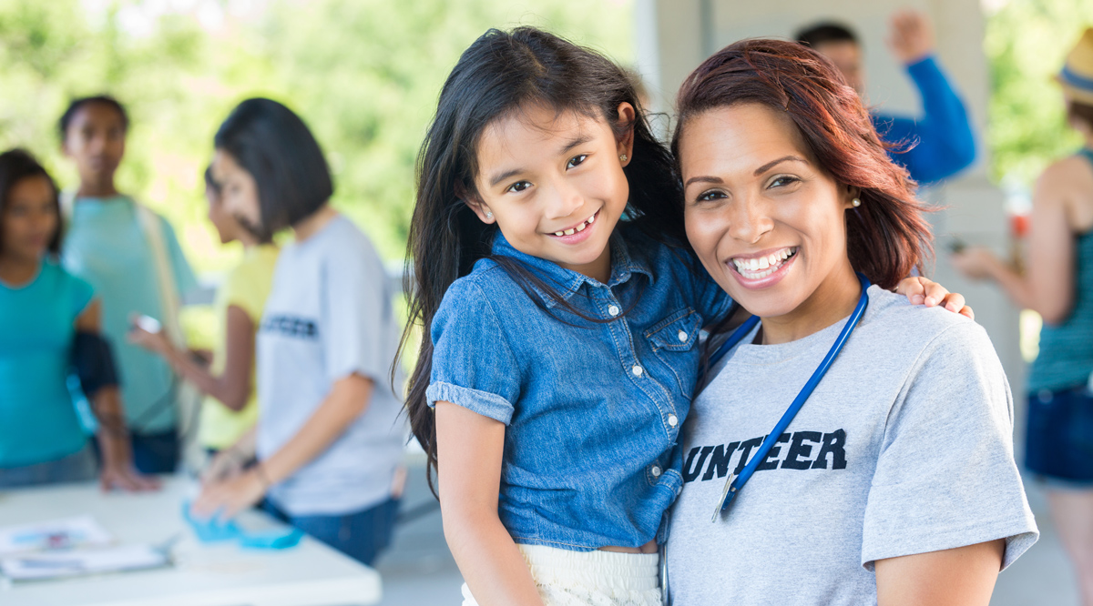 A smiling doctor holding a child patient at an outdoor health fair.