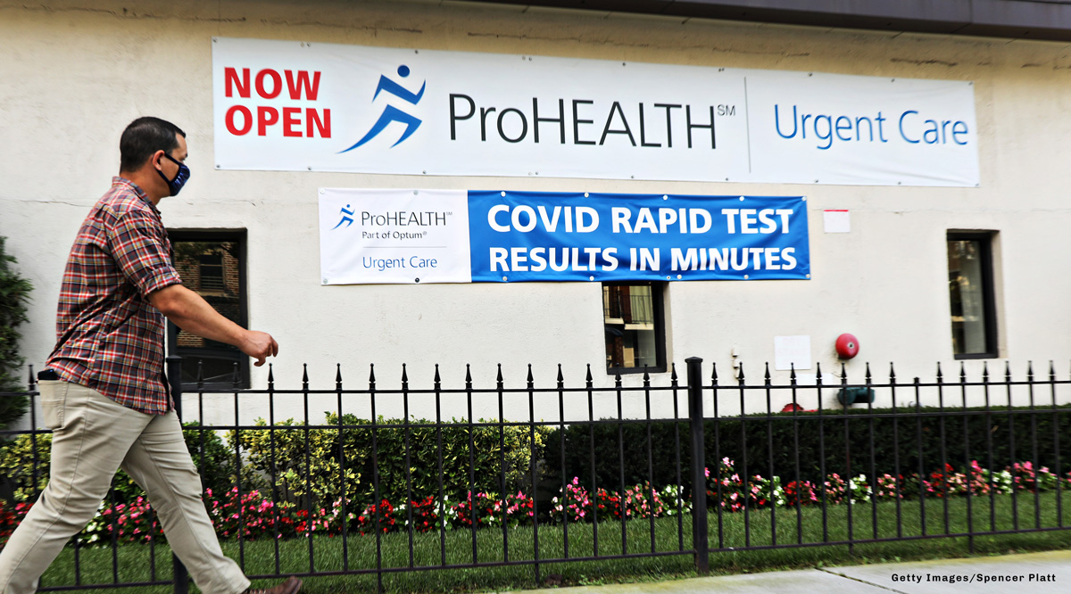 A man walking past a COVID Rapid Test sign