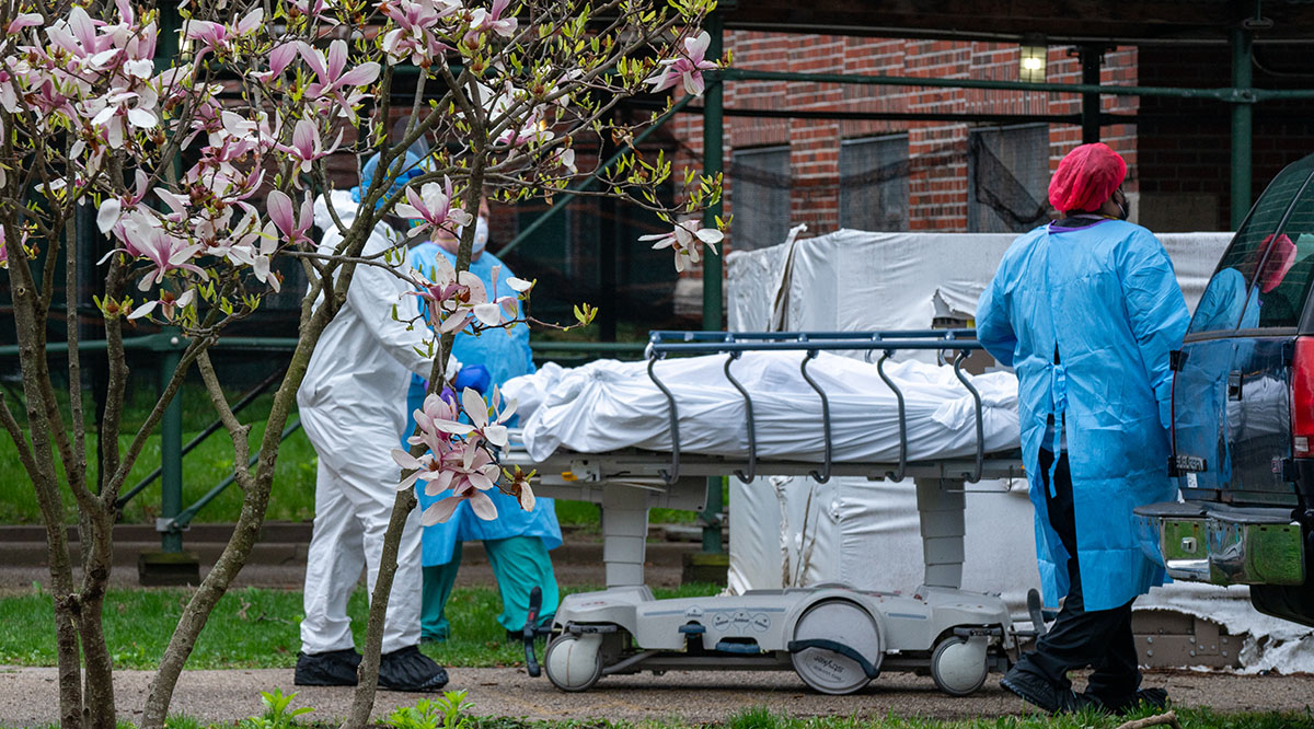Staffers at Kingsbrook Jewish Medical Center in Brooklyn, New York, transport a deceased patient to a refrigerated truck that the center had to use for the bodies of COVID-19 victims during a surge in the spring of 2020.