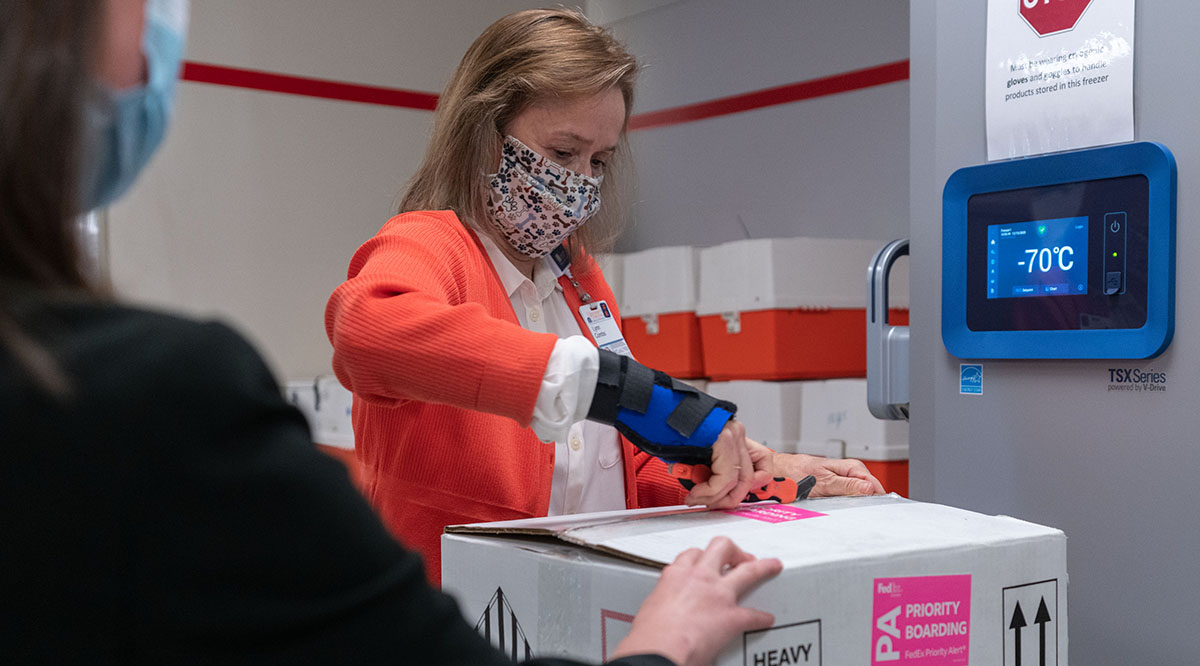 Lynn Combs, medication procurement coordinator at the University of Virginia Medical Center Pharmacy, unpacks the first shipment of COVID-19 vaccines for storage in a freezer set at minus 70 degrees Celsius.