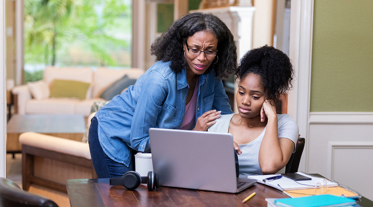 A mother looks at a computer screen with her daughter who looks upset