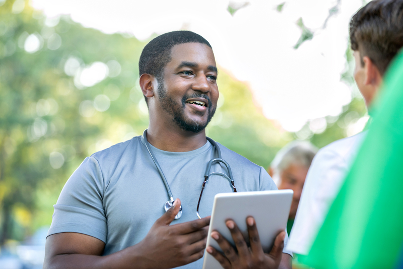 Doctor talks with community member during outdoor health fair