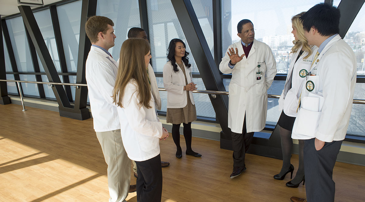 Selwyn Vickers, MD, senior vice president of medicine and dean of the University of Alabama School of Medicine, talks with students before the pandemic