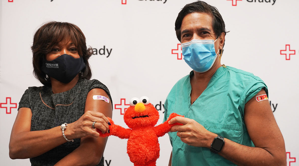 Valerie Montgomery Rice, MD, president and dean of Morehead School of Medicine, and medical correspondent Sanjay Gupta, MD, celebrate their COVID-19 inoculations with Elmo, who has been deployed to help answer children's questions about the vaccines.