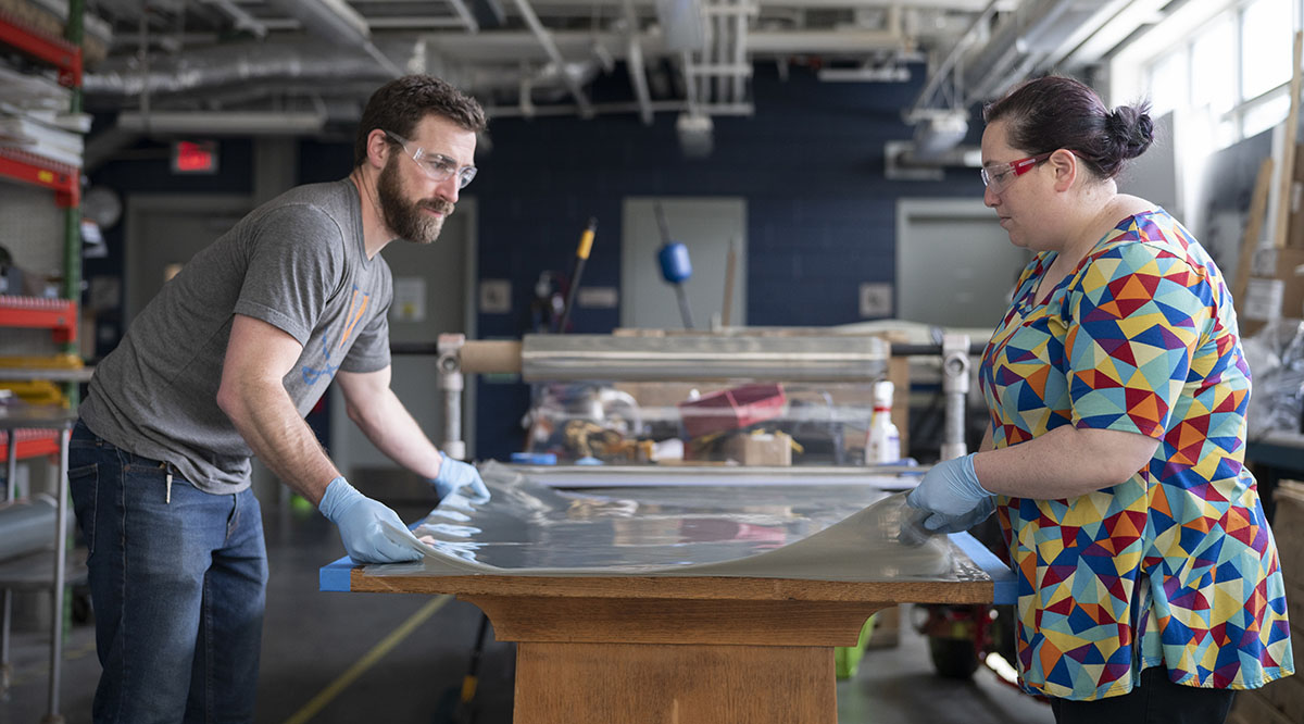 Trevor Kemp, assistant manager of the University of Virginia School of Architecture's FabLab, and Melissa Goldman, manager of the FabLab, prepare plastic film to be cut for face shields