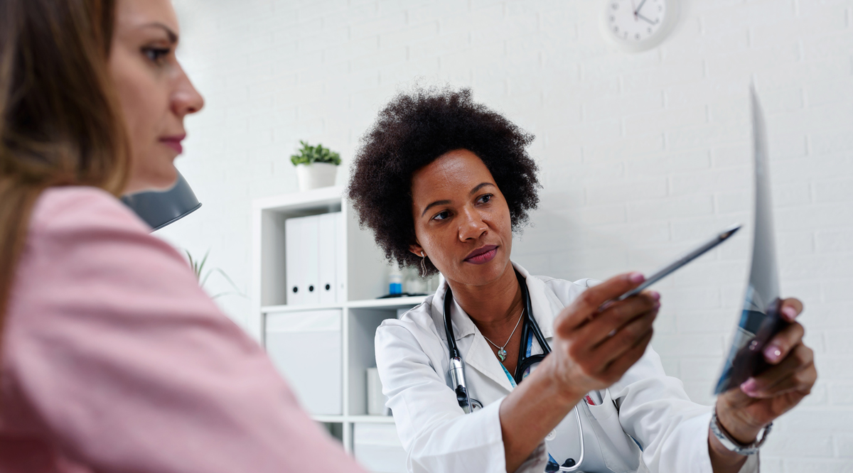 Female doctor talking with patient at desk in medical office.