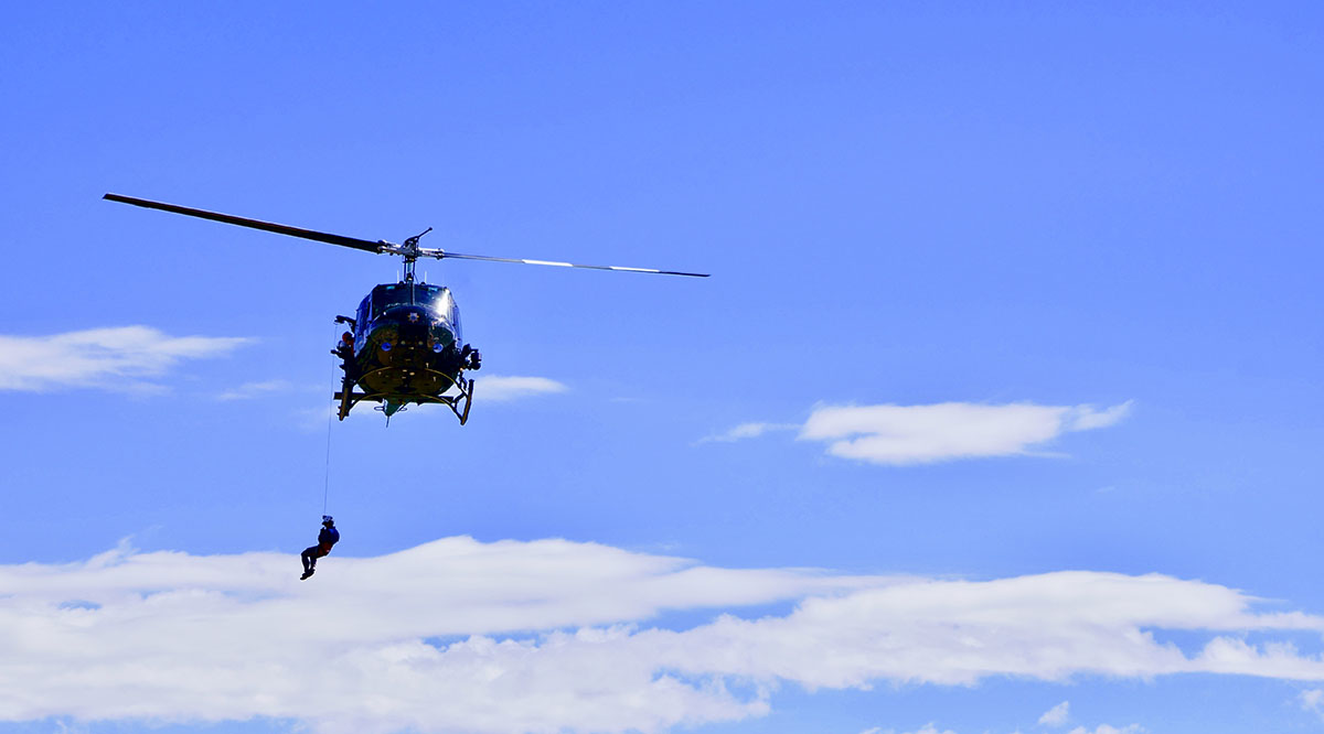 A resident trainee at the University of New Mexico International Mountain Medicine Center practices a helicopter hoist rescue maneuver