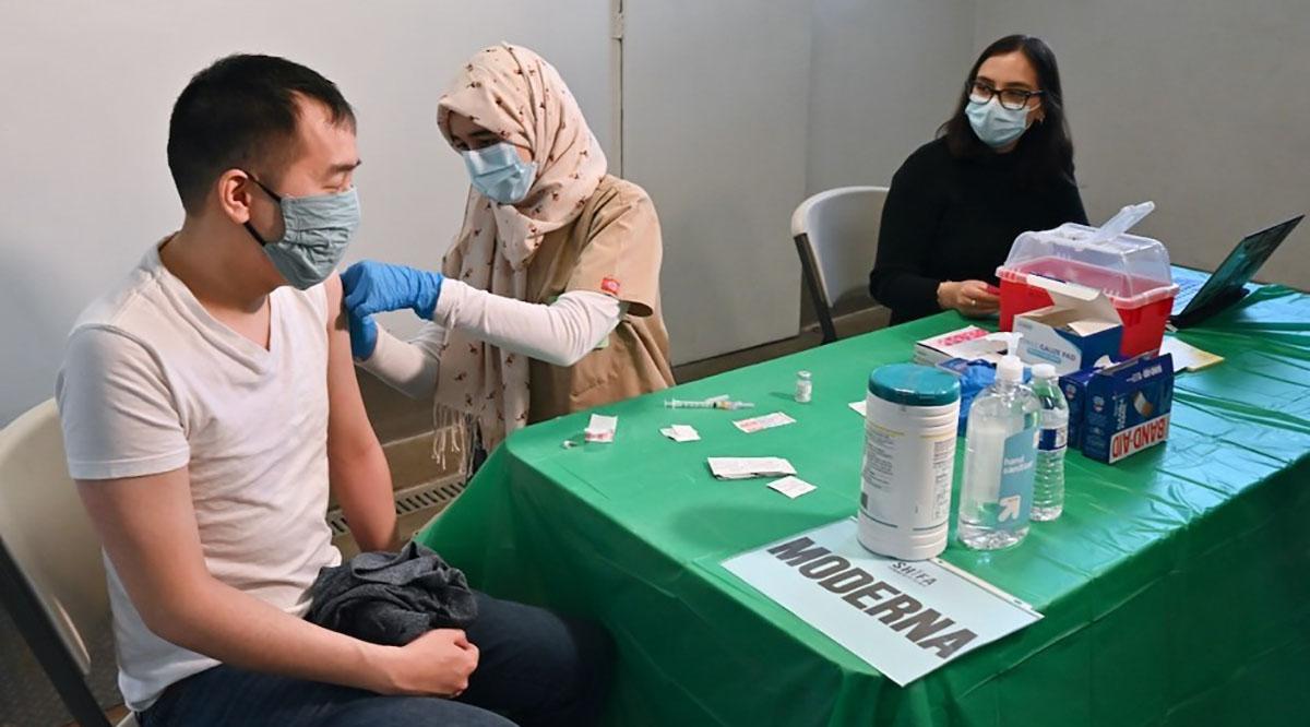 Justin Lau gets a bandage after his COVID-19 shot from UC Davis medical student Khadija Soufi at Shifa Community Clinic in Sacramento as undergraduate student Dana Hazem looks on.