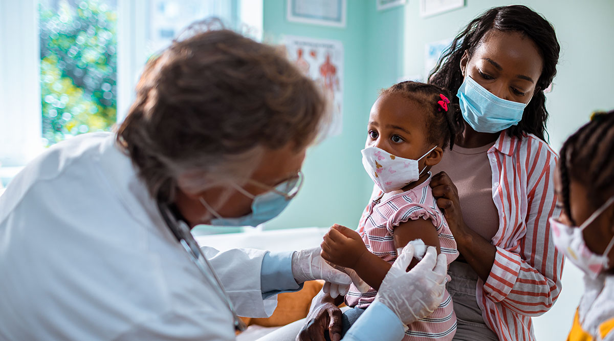 A child receives a vaccine from a doctor
