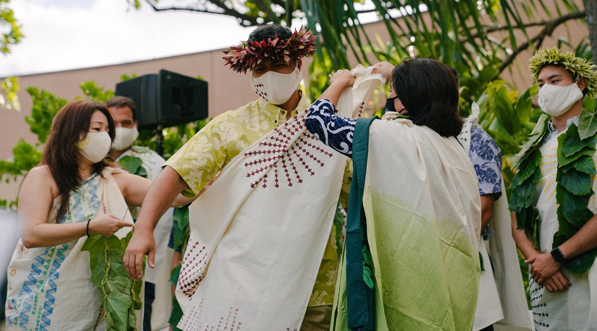 A student is flanked by two faculty members at the University of Hawaii at Manoa John A. Burns School of Medicine's Kihei Ceremony, held the day before commencement. Each Native Hawaiian medical student makes their own kihei to tell the story of their journey to medical school.
