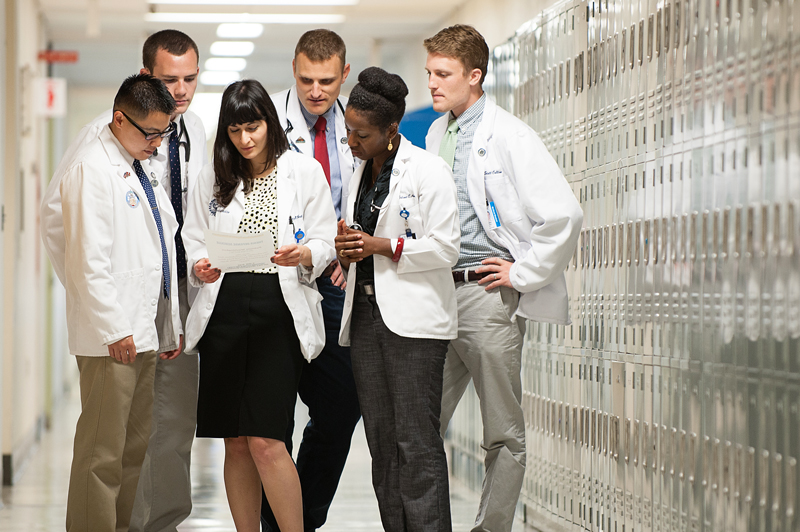 A group of medical residents standing in a hallway and looking down at a piece of paper.