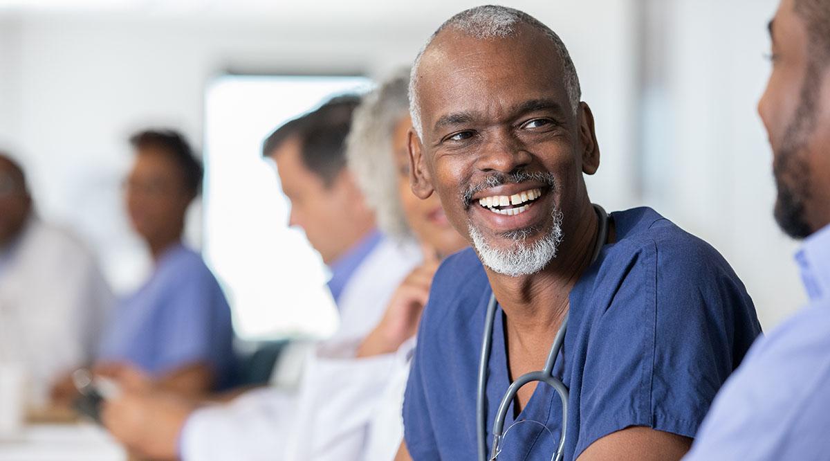 An older medical student smiles