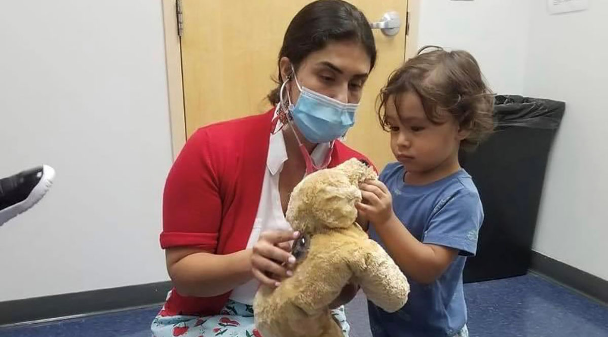 Paola Portela, MD, chief medical officer of the Infant Welfare Society of Chicago, plays with a young patient.