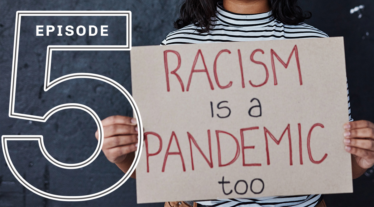 "A person holding a ""Racism is a Pandemic too"" sign"