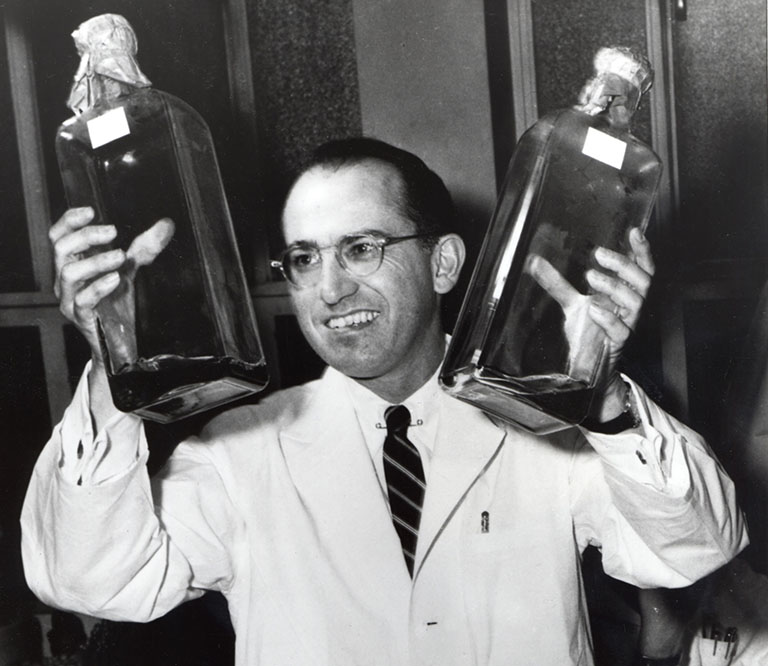 Jonas Salk holds two bottles of a culture used to grow polio vaccines in 1955