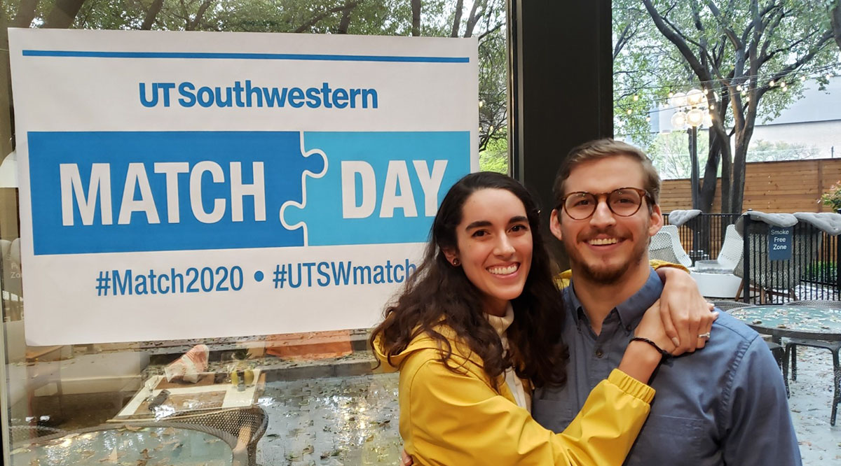 Christy Henderson, MD, and her husband pose in front of a banner provided by the University of Texas Southwestern Medical School for this year's virtual Match Day