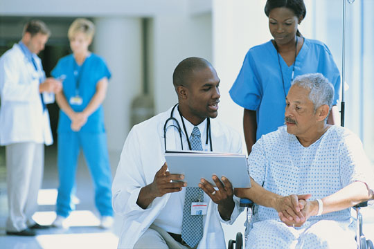 A doctor explains paperwork to a patient in a wheelchair while a nurse pushes him.