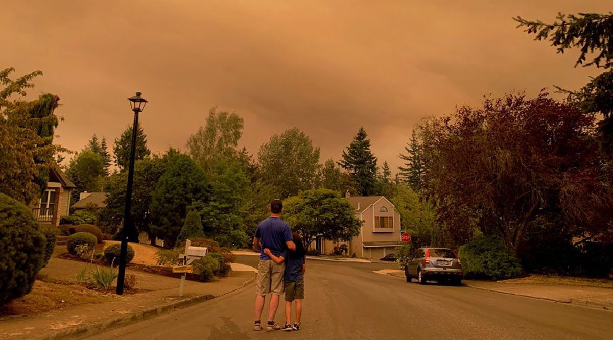 Portland residents step outside to view the wildfire smoke casting a colored haze over a neighborhood on Sept. 9, 2020.