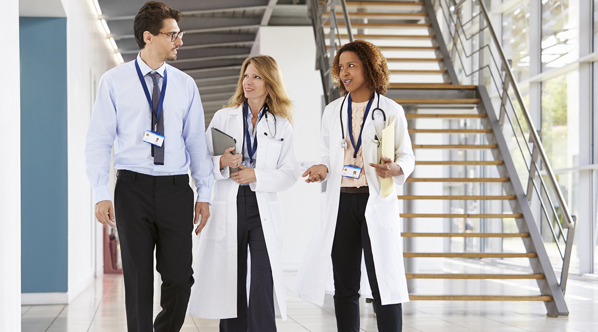 A male and two female doctor colleagues walk along a hallway.