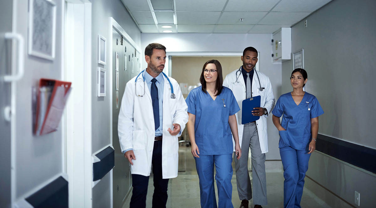 A group of male and female colleagues walk down a hospital hallway.