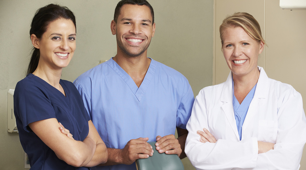 Three health professionals look toward the camera and smile.