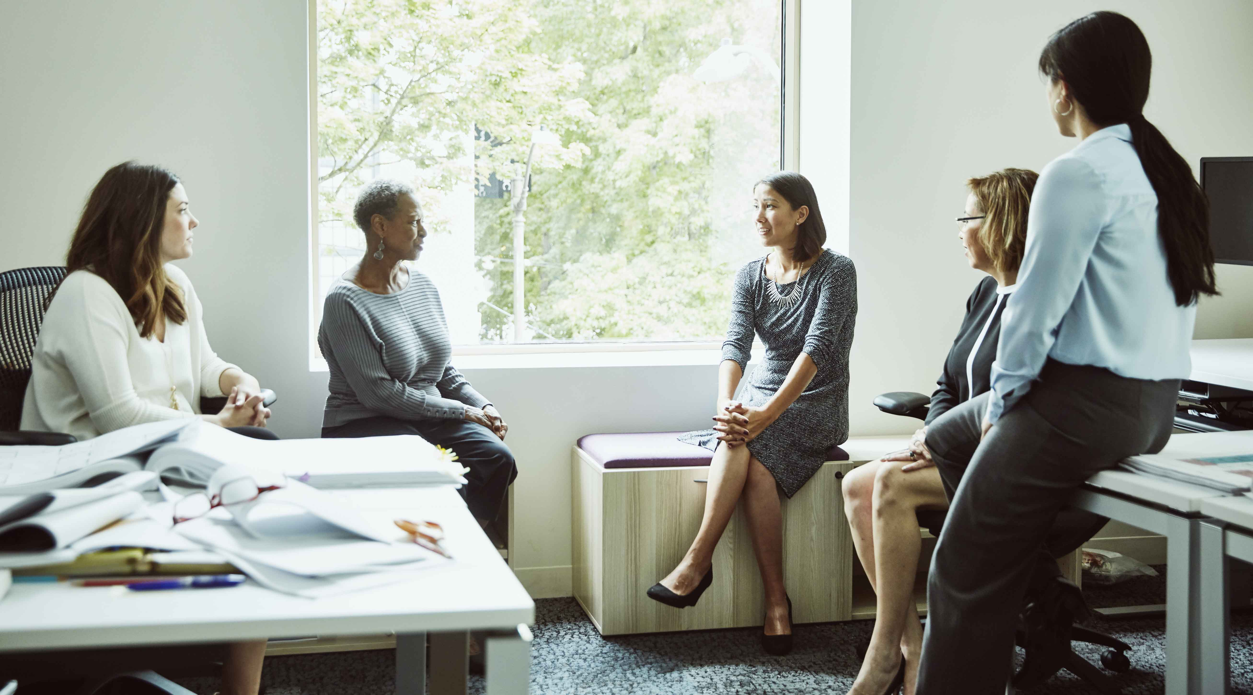A group of women sit in a circle and discuss work.