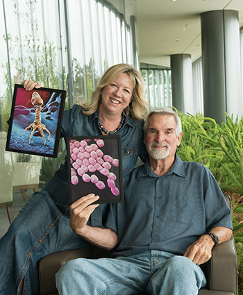 Steffanie Strathdee, PhD, and Tom Patterson, PhD, with photos of the life-saving phage and deadly bacterium.