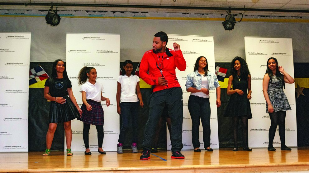 Henry Santos teaching dance moves at a New York City public school.