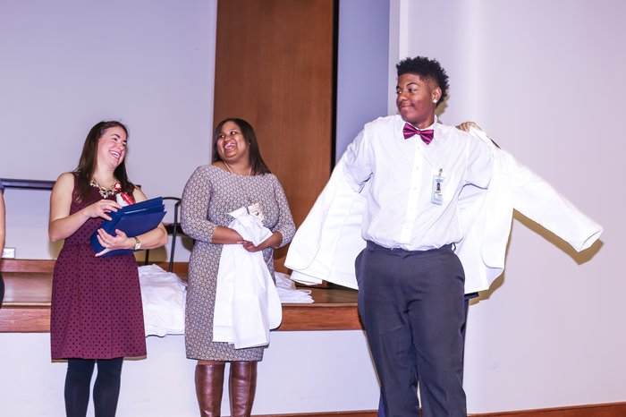 a student receives a white coat at the end of the program