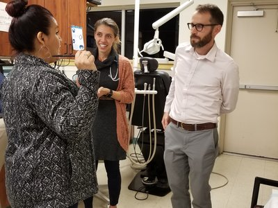 CHW Lidia Regino talks with resident Sarah Friedberg, MD, and attending physician David Armstrong, MD, at the One Hope clinic.