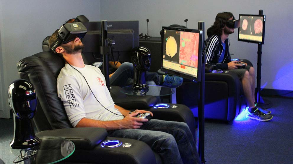 People in chairs wearing VR headset in front of screens