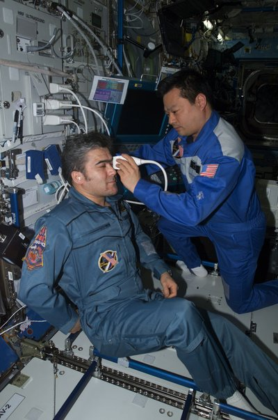 ISS Expedition Commander Leroy Chiao, PhD, performs an ultrasound examination of the eye on Flight Engineer Salizhan Sharipov.