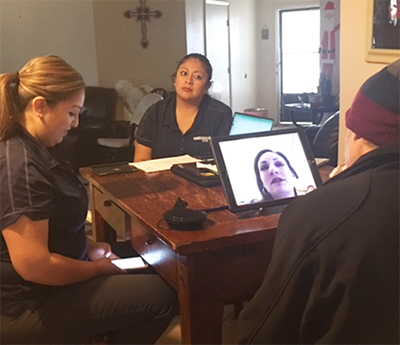 Home visit with 2 nurses and patient looking at computer on table
