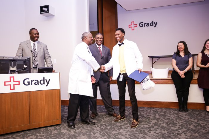 Drs. Omar Danner, Derrick Beech, and Ed Childs from Morehouse School of Medicine congratulating a student who completed the program.