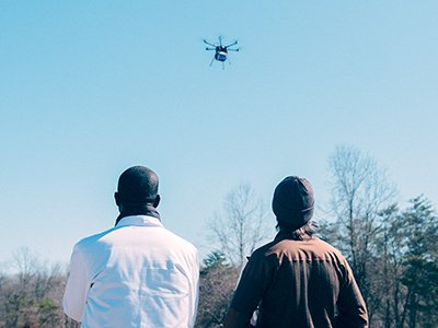 Dr. Timothy Amukele (left) and drone engineer Jeff Street from Johns Hopkins Medicine watch the drone take flight for their experiment.