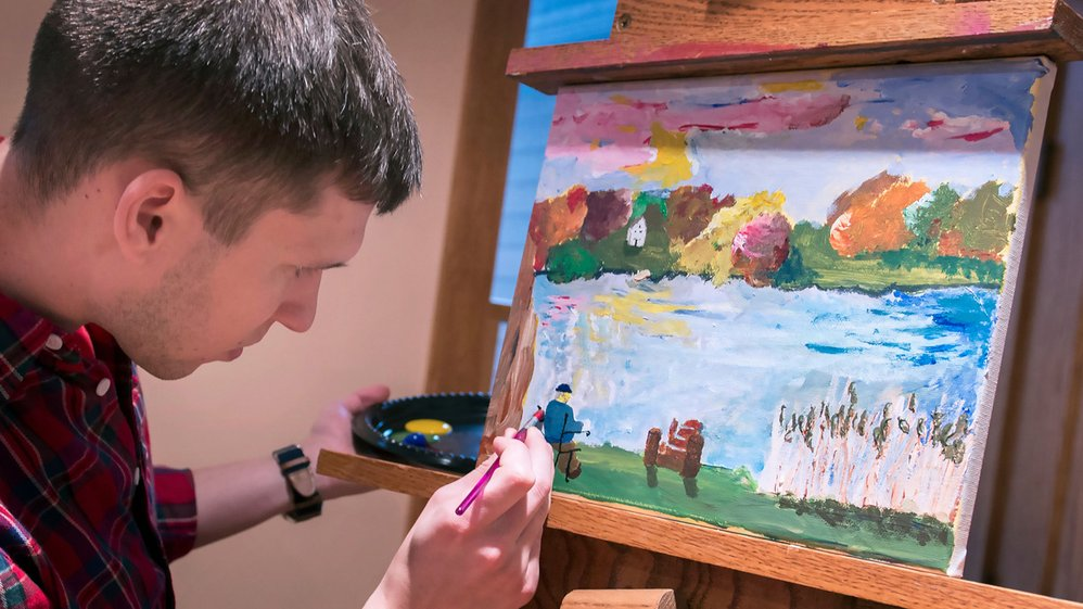 Penn State College of Medicine student Scott Paradise creates a copy of a Van Gogh painting based on a partner's description. The class emphasizes the importance of open-ended communication in medicine.