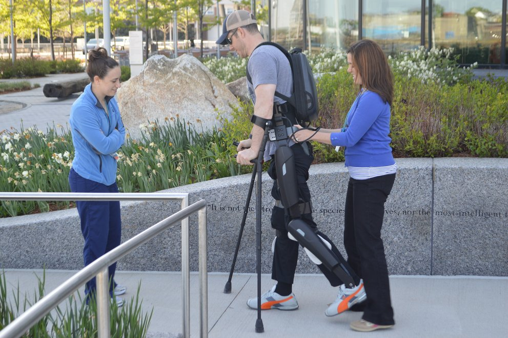 Two women assist man with crutches and exoskeleton