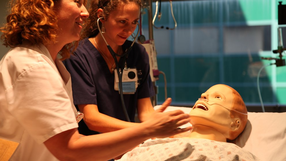 two medical students with a patient manikin