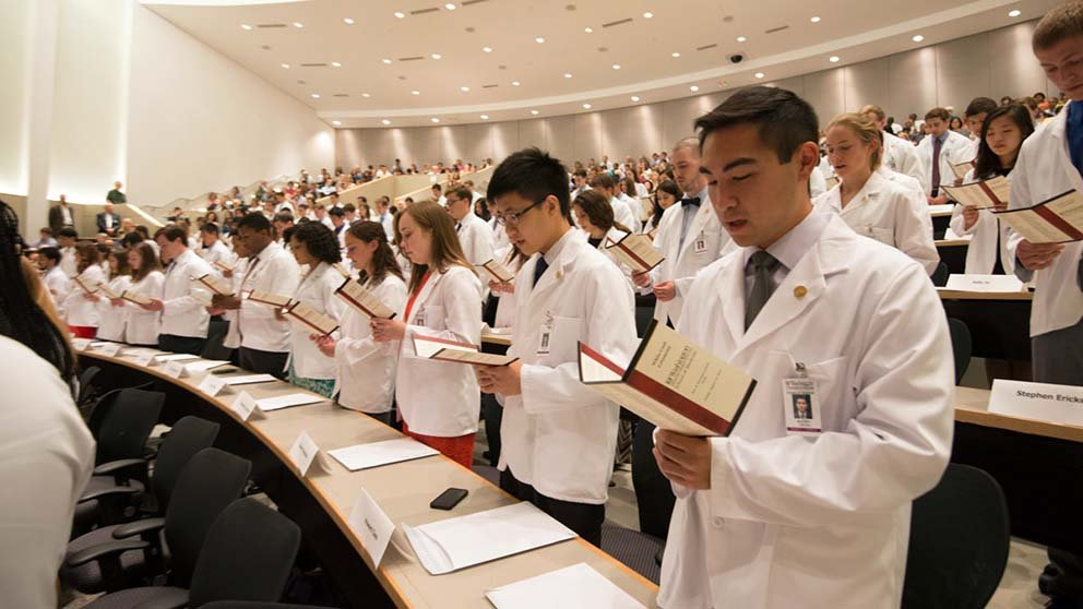 Medical students wearing white physicians' coats stand in a large room. They read a printed oath out loud for their white coat ceremony.