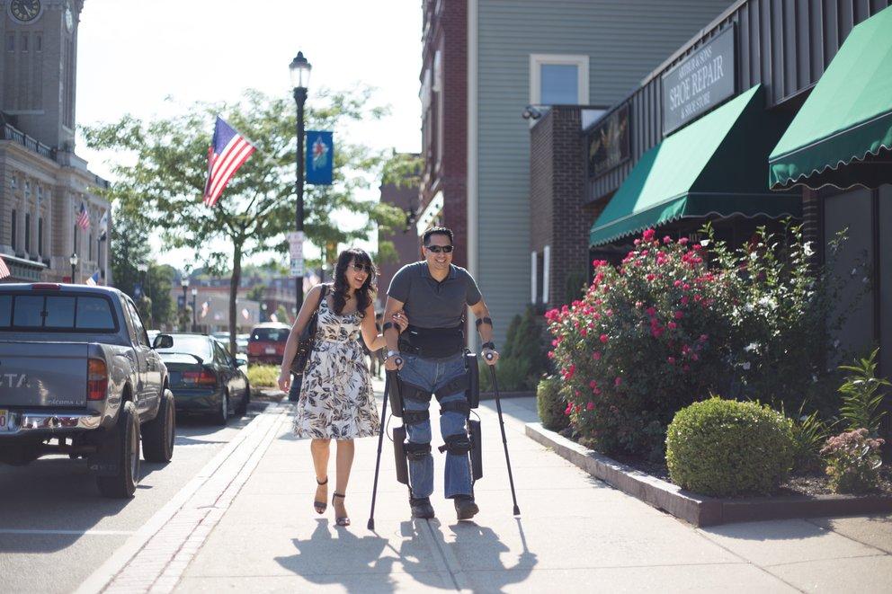 Man with exoskeleton walking with woman
