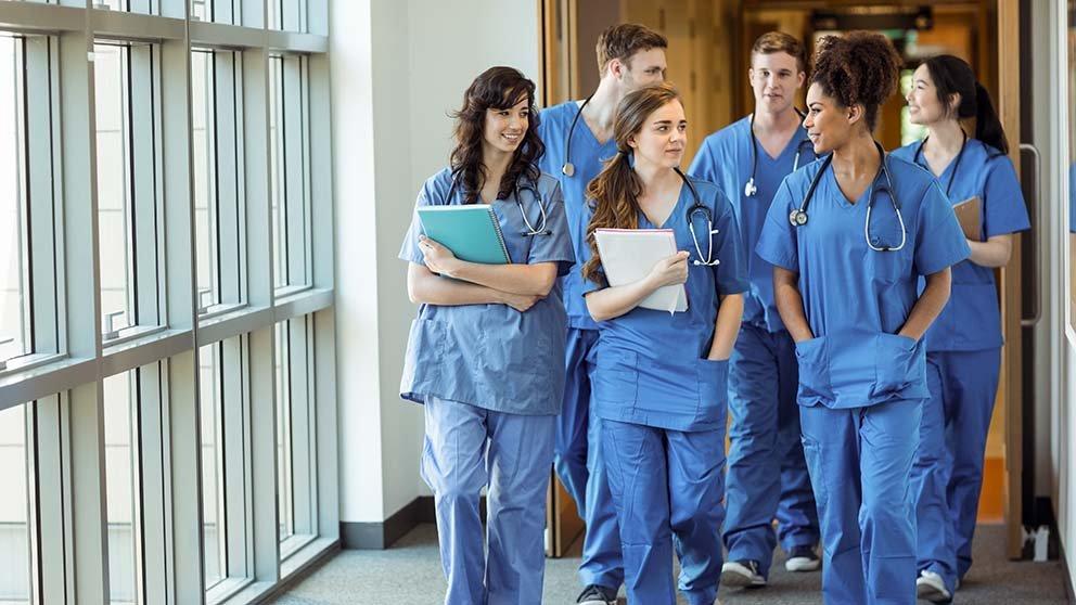 doctors in scrubs walking down a hallway