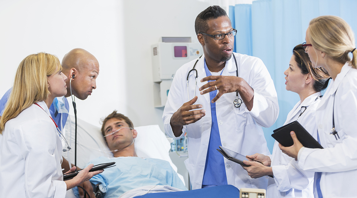 Doctor giving instructions to medical students while seeing a patient