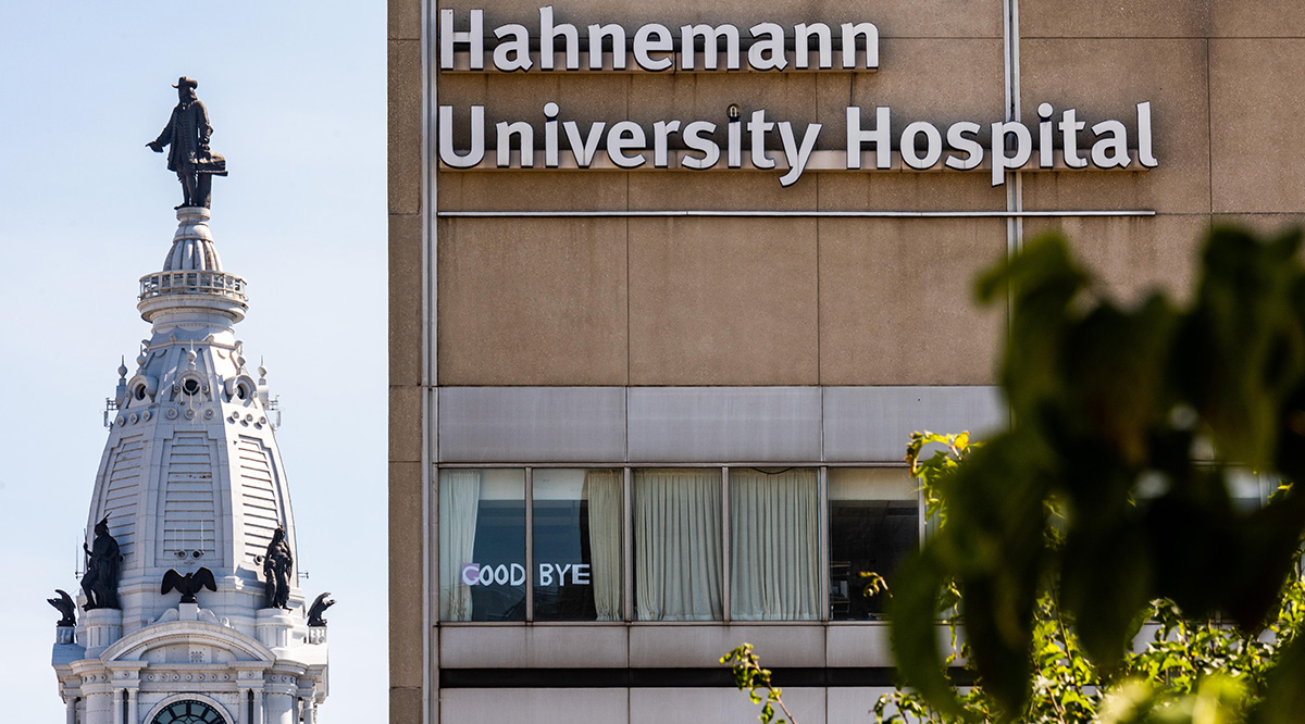 "A photo taken July 15, 2019, of Hahnemann University Hospital and Philadelphia City Hall shows a small sign declaring ""Goodbye""."