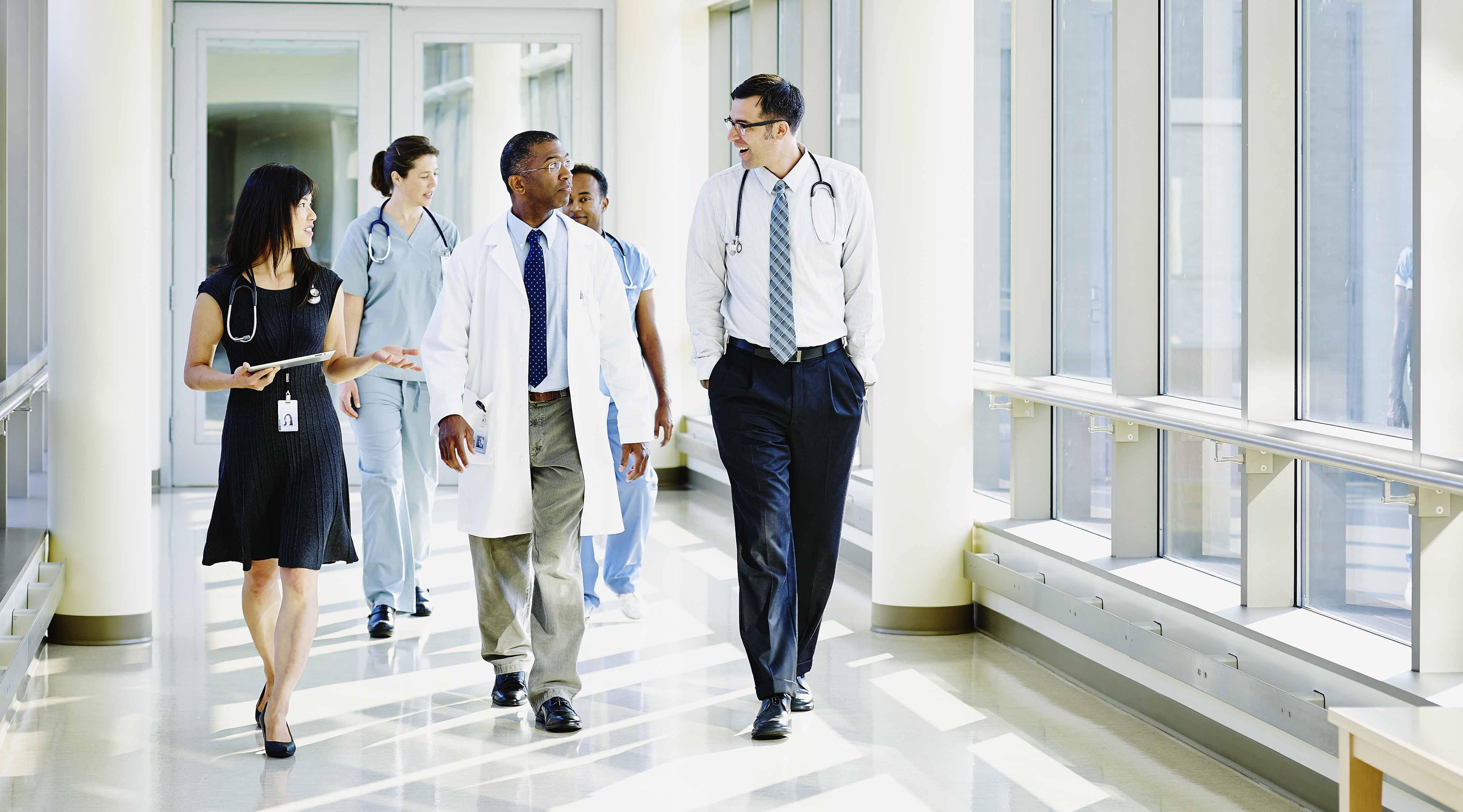 A group of doctors have a conversation while walking down a hallway.