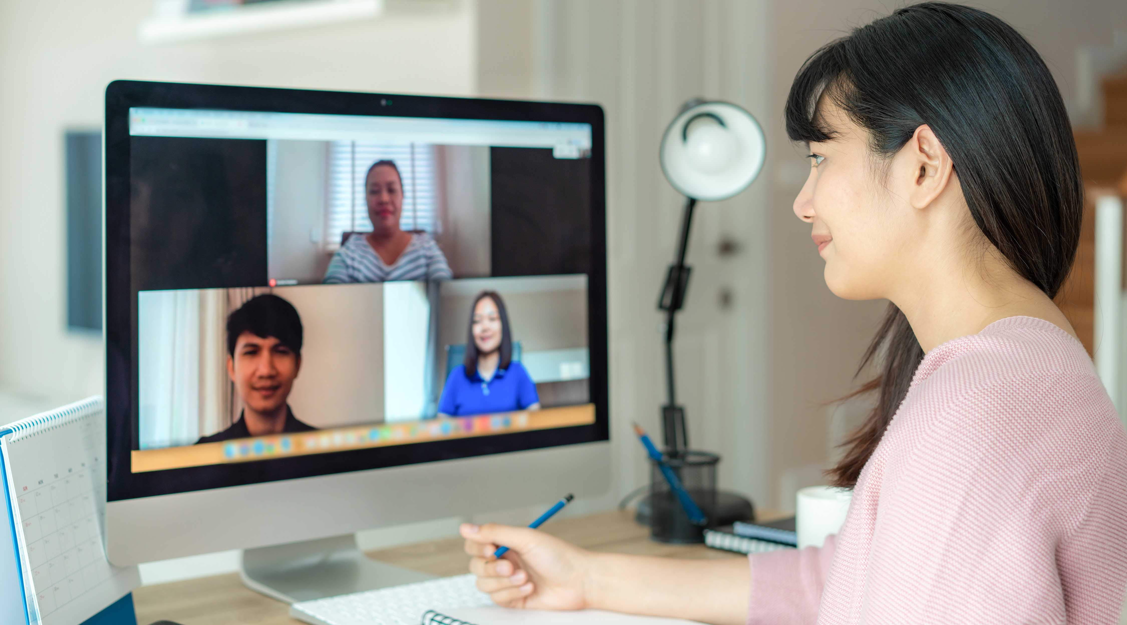 A woman leads a meeting over video chat.