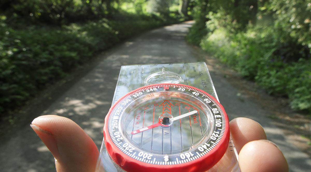 A person holds a compass on a path